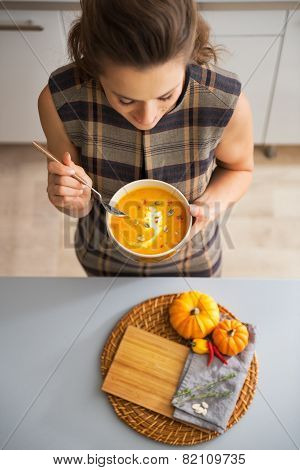 Closeup On Young Housewife Eating Pumpkin Soup