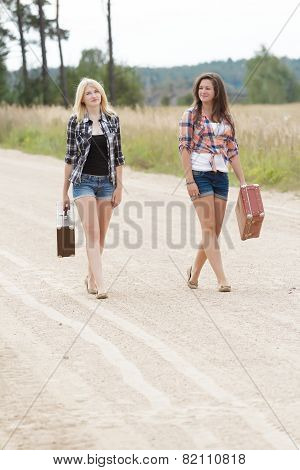 Blonde And Brunette Friends Walking On Road