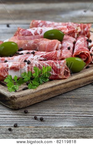 Various Meats On Serving Board With Rustic Background