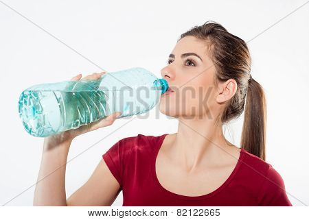 Woman drinking water from the bottle.