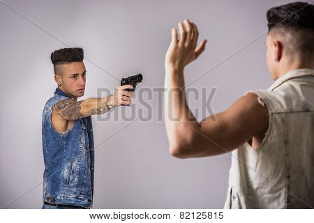 Young Man Pointing a Gun to Another Guy