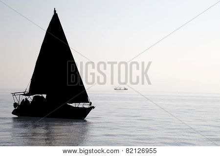 Sailboat silhouette at the sea in a foggy day. Yachting tourism - maritime
