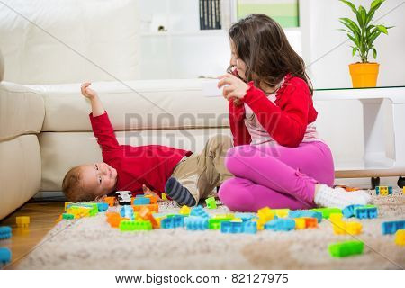 Two children playing on the carpet. Girl holding phone. Selective focus