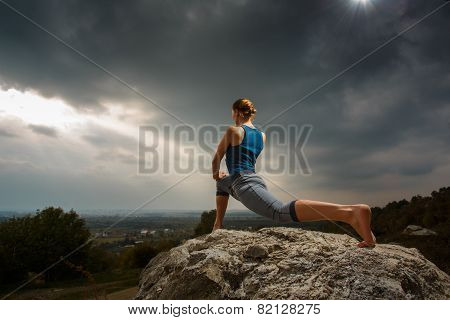 Woman doing yoga against the setting sun