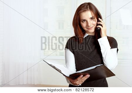 Girl Holds A Black Folder Open In One Hand And In The Other She Holds The Phone On Which She Says An