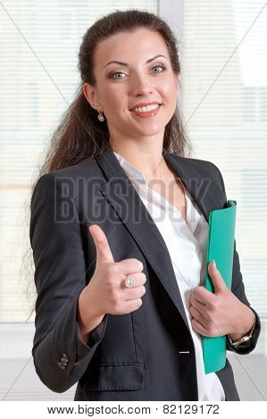 Woman In A Jacket Shows That All Ok And Holding Her Hand A Green Folder