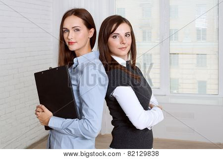 Two Women Standing Back To Back Against The Window