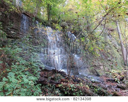 Waterfall On A Cliff In The Forest