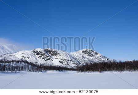 View of a winter valley between mountain ridges.
