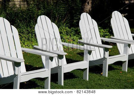 Row of white Adirondack chairs