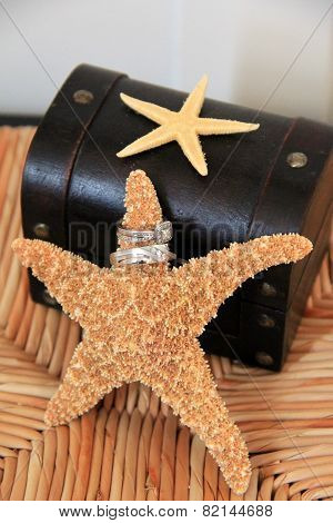Wedding rings on starfish on cane chair