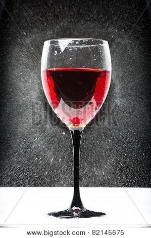 glass with red wine. splashing water