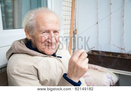 Smiling Old Man Holding A Cigarette