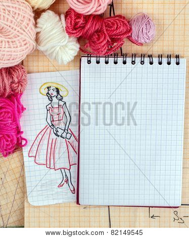opened notebook with a draft scetch fashion dress