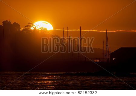 Silhouette Of Ships Masts Against Sunset Over A Harbor