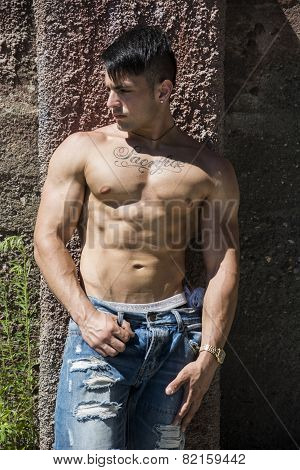 Shirtless muscular young man outdoor against concrete wall