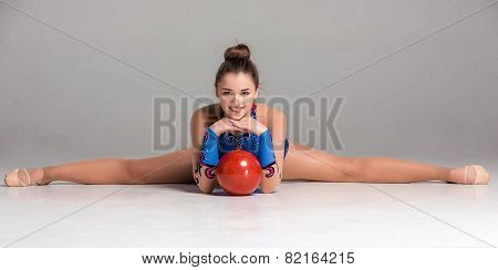 teenager doing gymnastics exercises with red gymnastic ball
