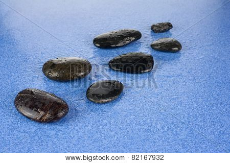 Black Spa Stones On Blue Background.