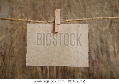 Old Sheet Of Paper Hanging On The Clothesline On Clothespin . On Old Wood Background.