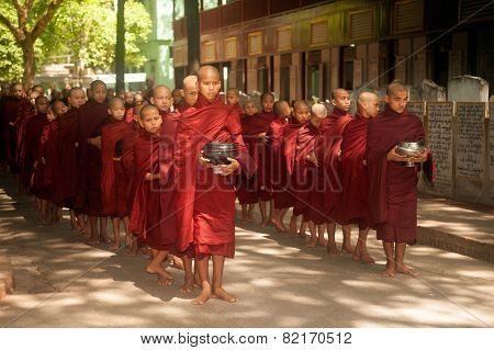 Row Of Buddhist Monks Waiting Lunch.