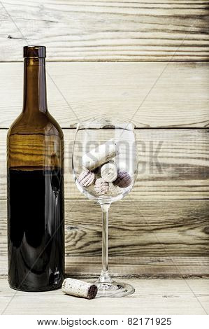 Wine glass, corks and bottle on a wooden background