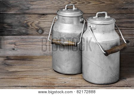 Aluminum old milk cans on a wooden background in the horizontal format