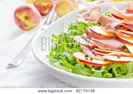 Arugula with bresaola and nectarine on white plate