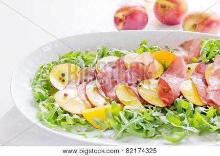 Bresaola with nectarine,arugula on white ovale plate