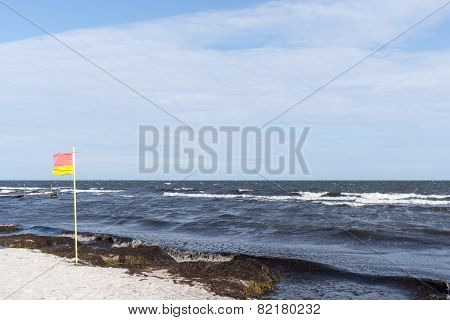 Red And Yellow Beach Flag Flapping In The Breeze