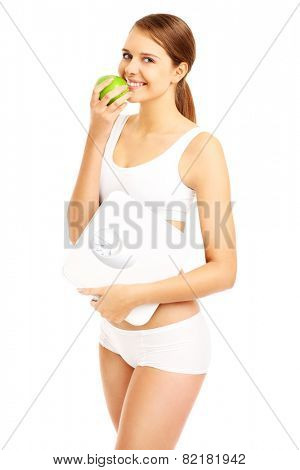 A picture of a fit woman with a green apple and bathroom scales over white background