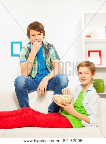 Happy boys eat popcorn while sitting on white sofa