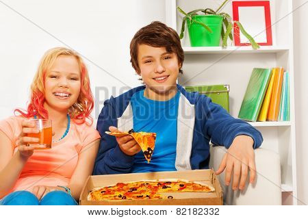 Happy girl and boy hold pizza pieces on white sofa