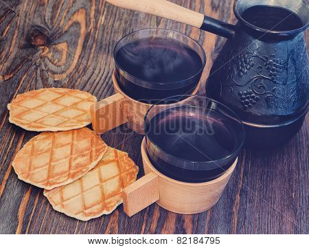 2 cups of coffee on a wooden background, cookies and a coffee maker