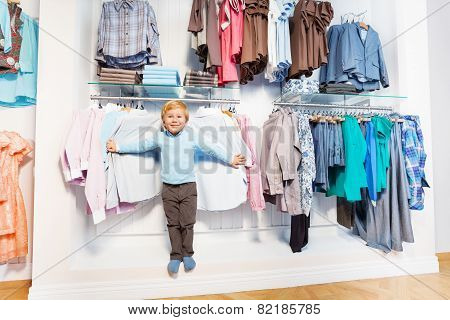 Cute boy stands among clothes on hangers and shelf