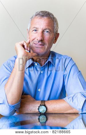 Successful mature handsome businessman waiting for you for an interview