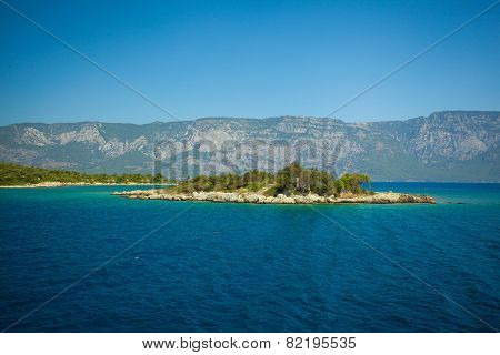 island on a background of blurred sea with mountain views
