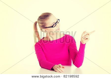 Young casual woman by a desk pointing aside.