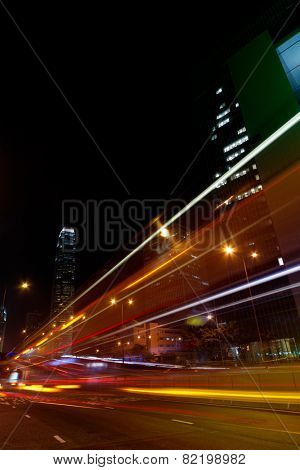 Colorful city night scene with modern skyscrapers and cars motion blurred in Hong Kong, Asia.