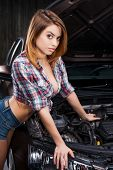 stock photo of cleavage  - Attractive young woman with beautiful cleavage leaning at the car in auto repair shop - JPG