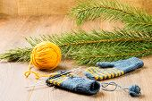 pic of pine-needle  - ball of threads knitting needles mittens and branch of pine on wooden background - JPG