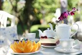 picture of opulence  - A man having a afternoon tea and cakes and fruit orange in the garden - JPG
