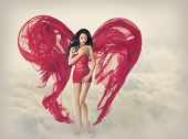 pic of broken hearted  - Woman Angel Wings as Heart Shape of Fabric Cloth Fashion Model Girl in Red Dress Flying on Fantasy Sky Clouds Background - JPG
