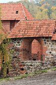 pic of red roof tile  - Arched brick red entrance to the fortress in Vilnius - JPG