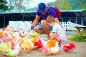 picture of feeding  - happy family feeding colorful pigeon birds on farm - JPG
