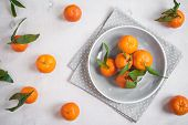 picture of clementine-orange  - Clementine tangerines with green leaves on white wooden background in a gray bowl - JPG