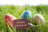 picture of happy easter  - Colorful Easter Background With Three Easter Eggs And Label With English Text Happy Weekend On Green Grass For Happy Easter Seasons Greetings - JPG