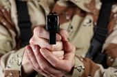 stock photo of soldier  - Close up horizontal image of pistol pointing forward with armed male soldier in background - JPG