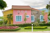 stock photo of grass area  - The colorful houses with green grass garden found near the road - JPG