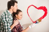 picture of wall painting  - Young happy couple are painting a heart on the wall while doing repair at home - JPG