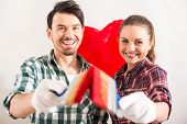 foto of mischief  - Portrait of young happy couple painted a heart on the wall while doing repair at home and looking at the camera - JPG